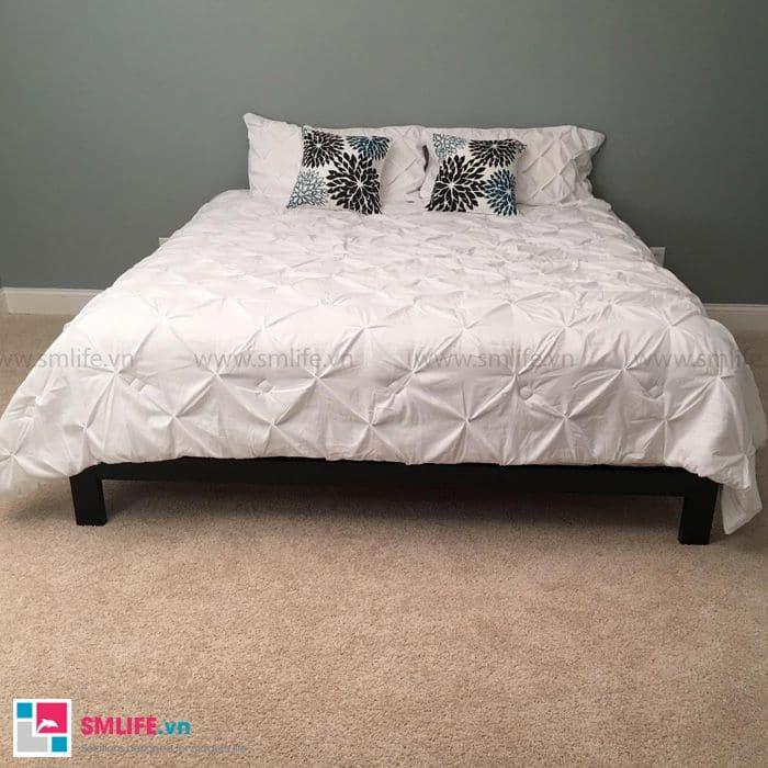 Phòng ngủ được trang trí bởi tấm đệm trắng và nổi bật với những chiếc gối hoa hòe